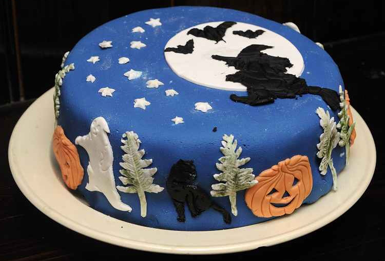 en ste pastel se usa una base de fondant azul para cubrir el pastel y sobre l se ponen figuras alusivas al festejo de halloween como son las
